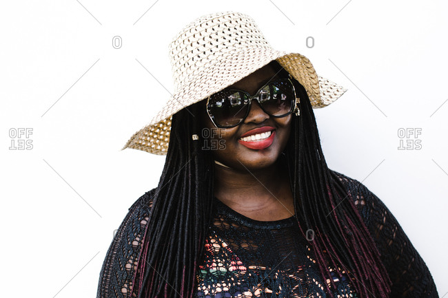 Woman wearing a floppy hat and sunglasses smiling in front of a white background