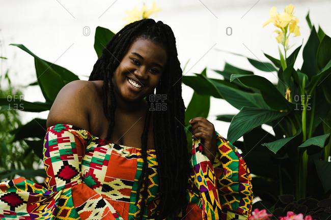 A medium shot of a black woman in a colorful African dress laughing with long braids