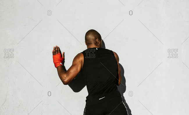 Black athletic man wearing red gloves leaning against a wall during workout
