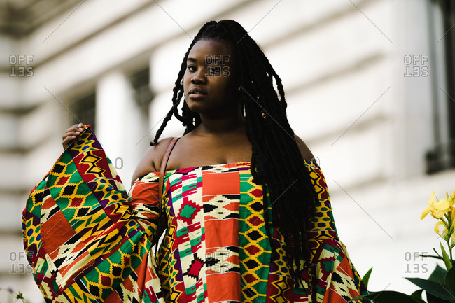 A medium shot of a black woman with long braids wearing a colorful African dress
