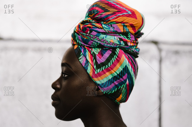 A side profile close up shot of an African woman wearing a multicolored headwrap