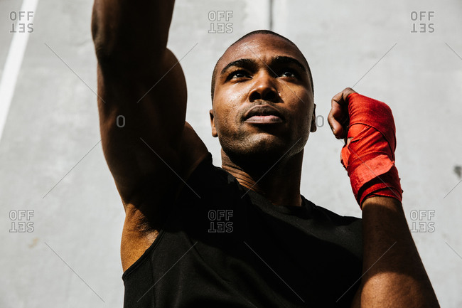Close up shot of a male boxer performing a right jab with his hands covered in boxing wraps