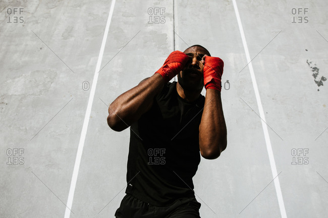 Male boxer performs a jabbing exercise with his hands covered in boxing wraps