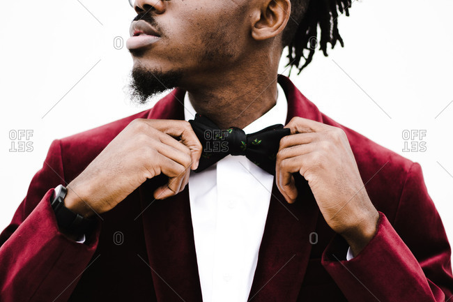 Horizontal close-up shot of a man in red suit with goatee straightening his bowtie