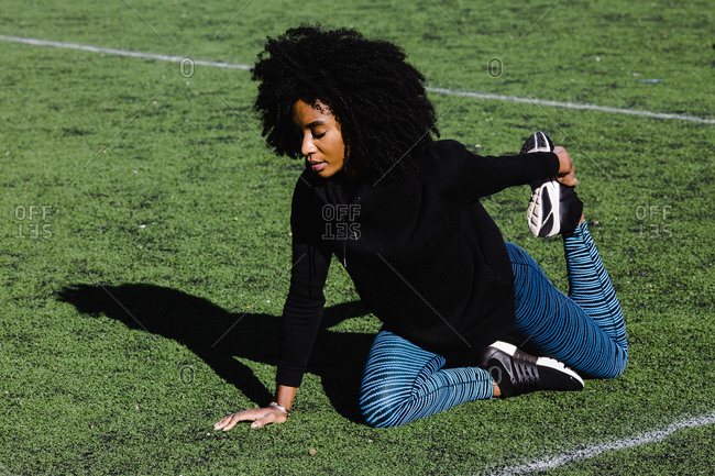 Black athletic woman with curly hair stretching her legs on a grass field