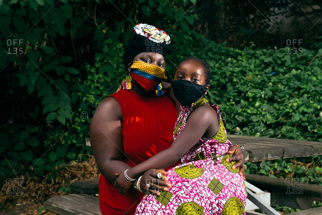 Young girl in black face mask sitting in her mother's lap and hugging her sitting on a park bench outdoors