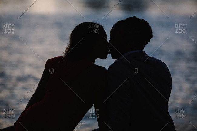 Horizontal silhouette of a young couple kissing seated by the waterfront