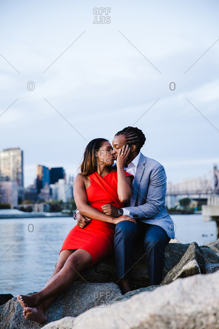Vertical full length shot of a passionate young couple kissing seated over the rocks by the waterfront