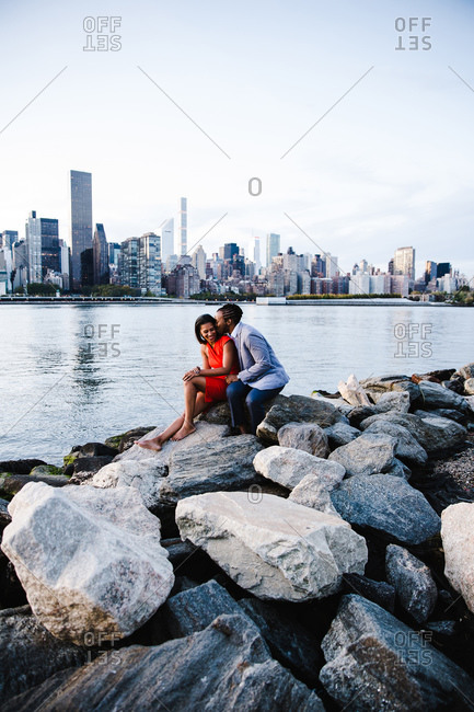 Wide shot of a young couple in smart casuals sitting over a boulder by the waterfront with the man giving a peck on the woman's cheek