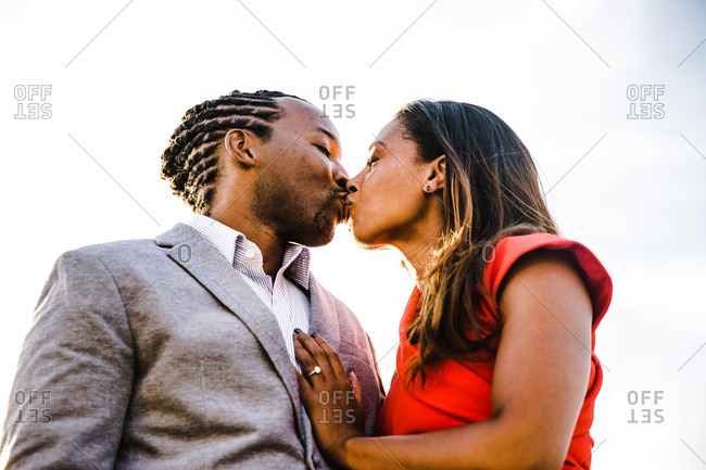 Low angle waist up shot of a young couple kissing