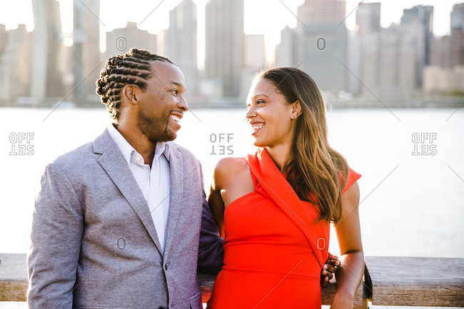 Horizontal shot of a black couple smiling at each other by the waterfront