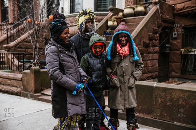 Full length shot of a black family of four in winter clothing laughing on a pavement
