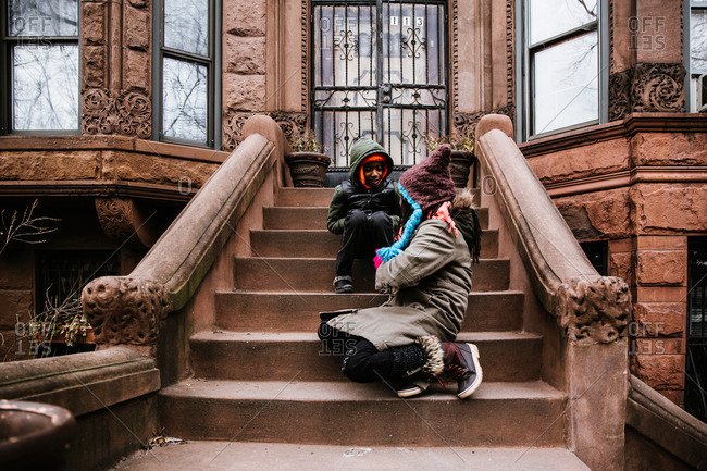 Horizontal candid shot of a black brother and sister sitting and talking on stairs in winter clothing
