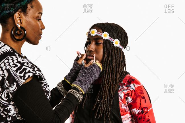 Black mom applying lip gloss on her daughter