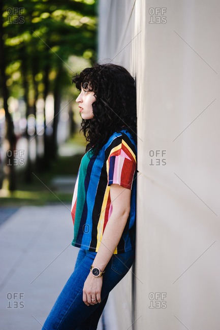 A side profile portrait shot of a young woman with curly hair and bangs leaning against a wall