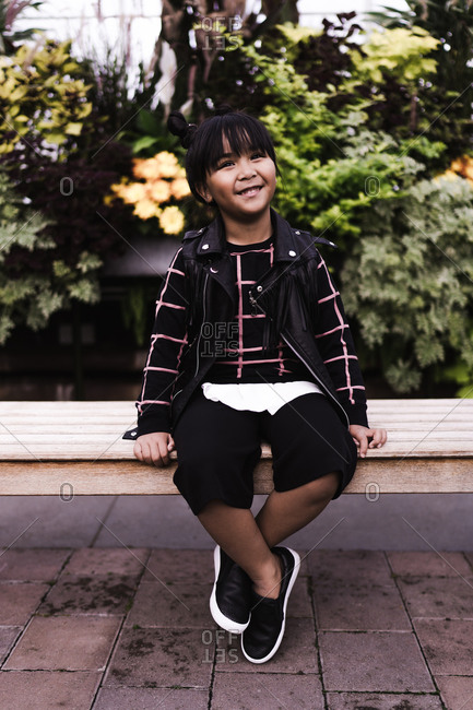 A portrait shot of a happy young Asian girl with pigtails sitting on a bench in a park