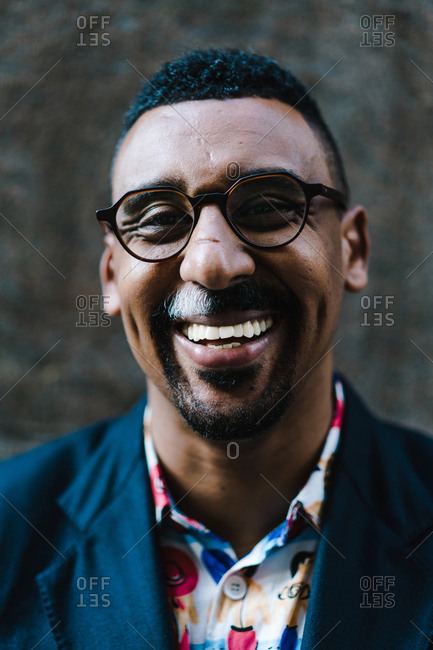 Vertical portrait of a businessman in suit smiling at the camera outdoors
