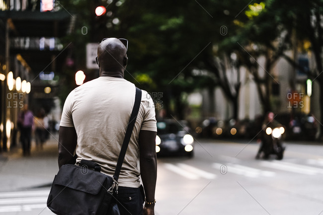 Black man with a satchel looking out into the city