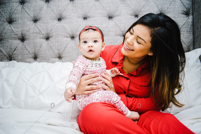 Horizontal portrait of a joyous latina mother holding her little daughter in Christmas pajamas over bed