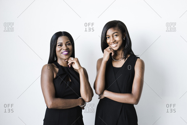 Horizontal portrait of mother and daughter in black gowns smiling at the camera on white background