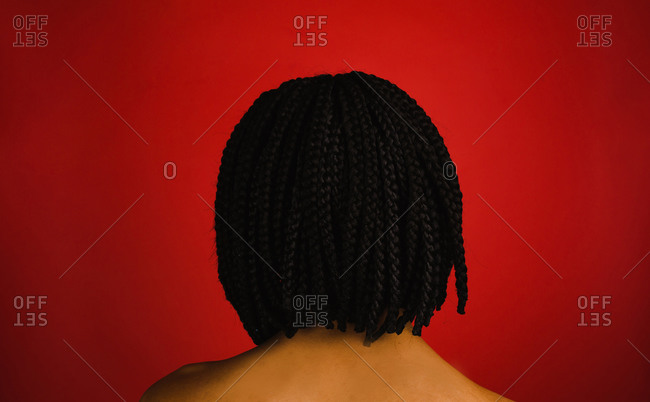 A back shot of a black woman with a short braided hairstyle on a red background