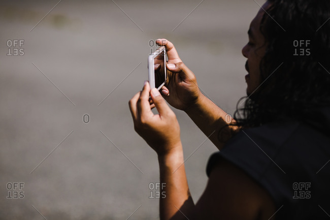 Native American coach with long hair taking pictures using a smartphone on a basketball court