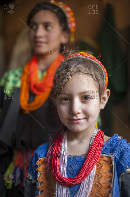 Kalasha valley, Chitral, North Western Frontier Province, Pakistan - November 11, 2008: The indigenous Kalasha People, here a girl and her older sister wearing traditional dress and headwear smile for the camera