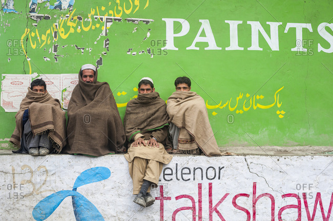 Chitral, North Western Frontier Province, Pakistan - November 14, 2008: Four men wrapped up to keep warm sitting infront of a colourful wall in Chitral