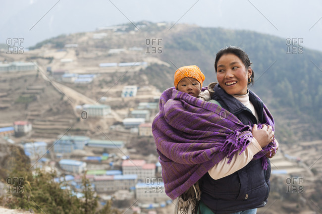 Namche Bazaar, Everest Regon, Khumbu, Nepal - April 7, 2009: A woman carries her baby in a blanket with Namche visible behind