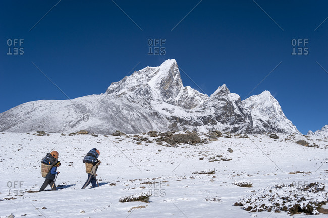 Tengboche, Khumbu, Nepal - April 10, 2009: Porters makes the long hard way up to Everest base camp carrying supplies in a traditional bamboo basket called a Doko with the massive peak of Cholatse visible in the distance