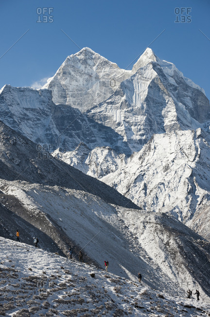 Khumbu, Nepal - April 10, 2009: Trekkers on their way to Everest base camp with views of Ama Dablam