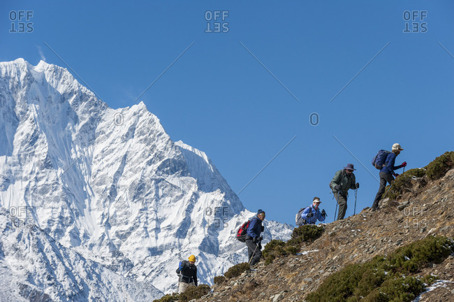 Khumbu, Nepal - April 10, 2009: Trekkers on their way to Everest base camp with views of Ama Dablam behind