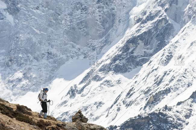 Khumbu, Everest region, Nepal - April 11, 2009: A woman makes her way back down from Everest base camp with a wall of snow and ice in the background