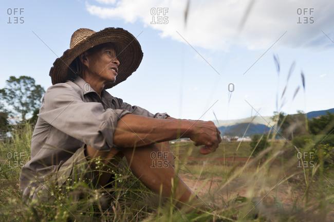Yuanmou, Yunnan, China - October 11, 2009: A farmer from Yunnan Province surveys his fields