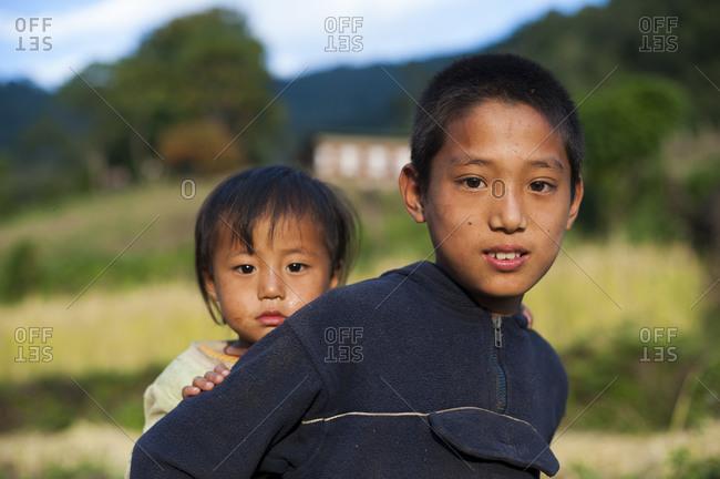 Laya, Gasa District, Bhutan - November 22, 2009: Two children from eastern Bhutan, a boy carrying his little sister