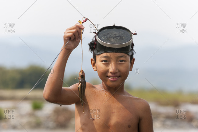 Putao, Kachin State, Myanmar - Mach 18, 2010: A little boy uses a basic mask to catch fish in the river near Putao in Myanmar