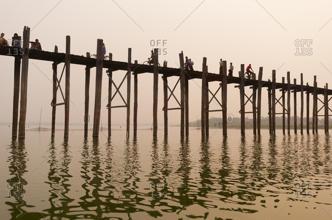 Amarapura, Mandalay District, Myanmar - March 26, 2010: The U Bein Bridge, a 1.2 km wooden footbridge (longest teak bridge in the world) built by the mayor U Bein salvaging the unwanted teak columns from the old palace during the move to Mandalay
