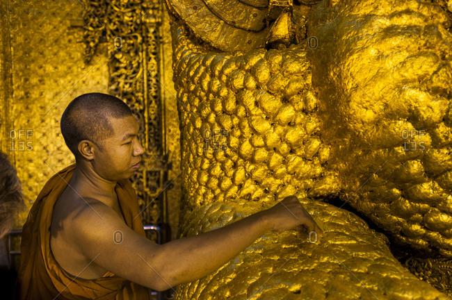 Mandalay, Mandalay District, Myanmar - March 26, 2010: A Monk applies gold leaf to a giant Buddha