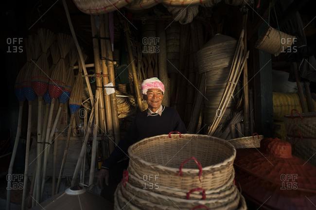 Kyaington, Keng Tung, Shan State, Myanmar - March 31, 2010: A man selling bamboo baskets and brooms at a market stall in Kyiang Ton