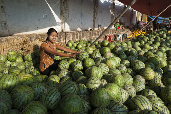 Inle Lake, Shan State, Myanmar - April 3, 2010: A woman sells watermelons from a market stall near Inle lake