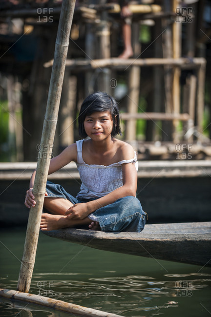 Inle Lake, Shan State, Myanmar - April 4, 2010: A Burmese girl rests on the end of a canoe on Inle lake
