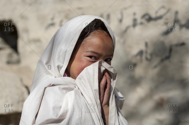 A school girl at Merchulu school in Pakistan hides her smile
