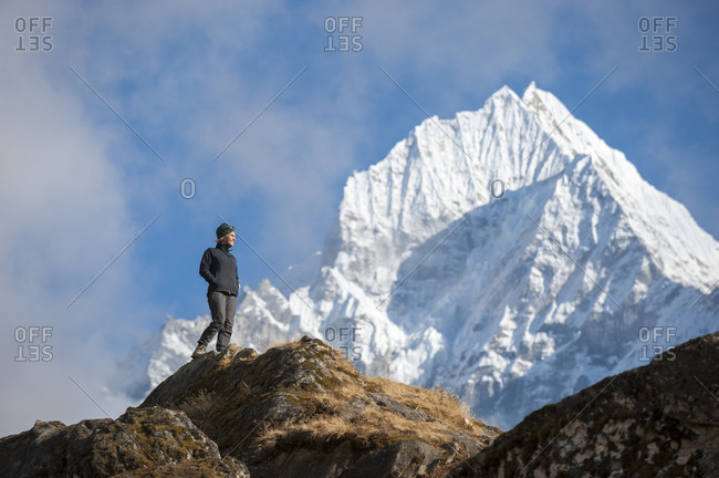 A trekker enjoys the views above Namche in the Everest region with views of Thermserku in the distance