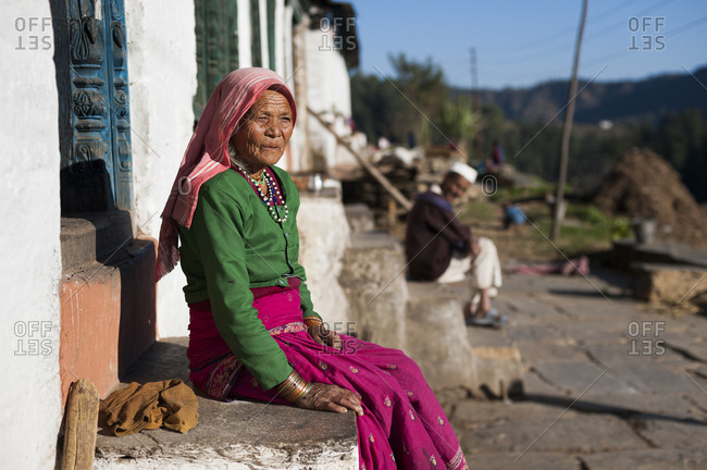 A old woman sits outside her house and watches the sun go down