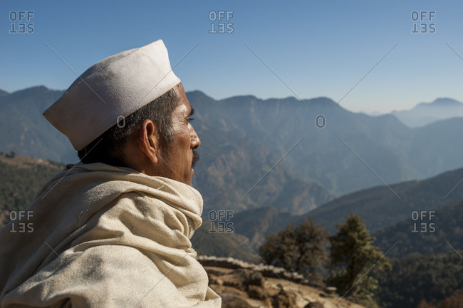 A man surveys the landscape from his little village in the hills of Uttarakhand