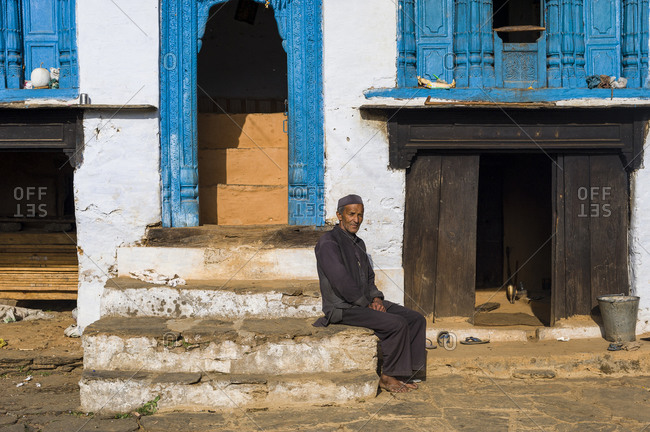 A old man sits outside his traditional style house in Uttarakhand