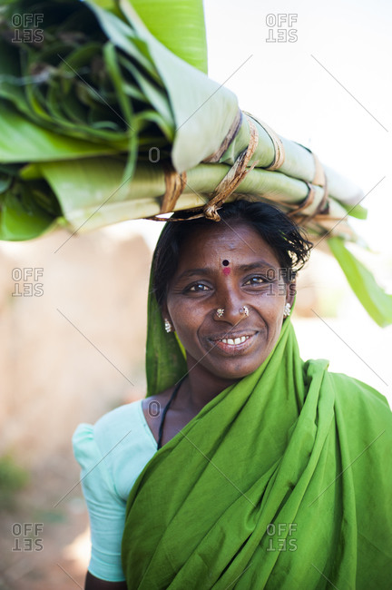 A woman carries a roll of banana leaves which will be used to wrap food