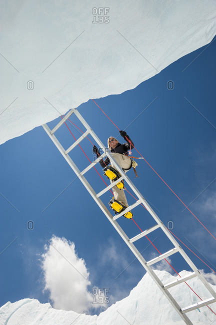 A climber makes her way across a crevasse using a temporary ladder