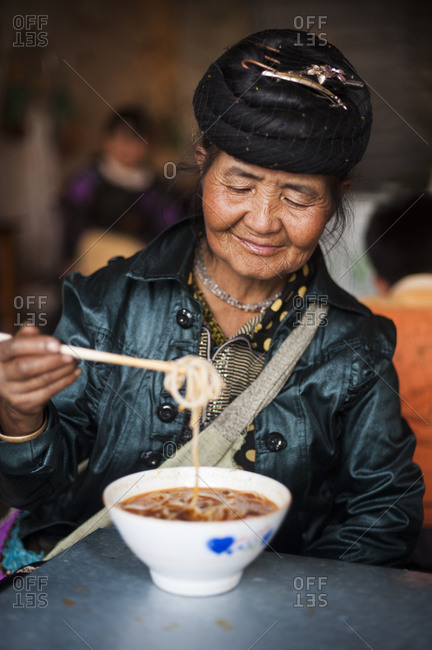 A Miao woman eats a bowl of noodles in the Yunnan province of China