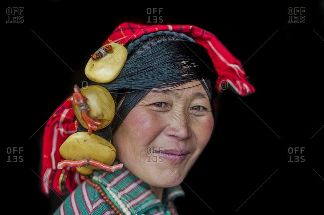 Ethnic Tibetan woman wearing traditional thread head dress and Dzi stones on her head